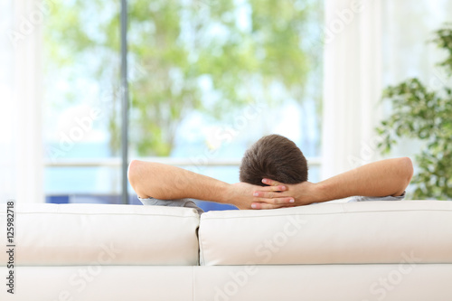 Deurstickers Ontspanning Man relaxed on a couch at home