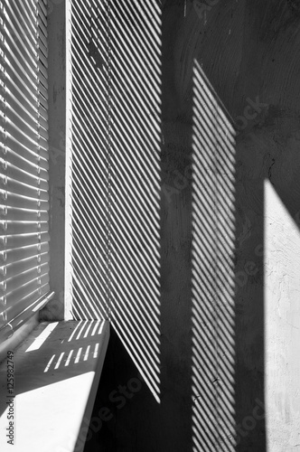 fototapeta na szkło Geometric black and white composition. The plane of the plaster wall with a structural graphic shadow falling from the blinds. Vertical view.