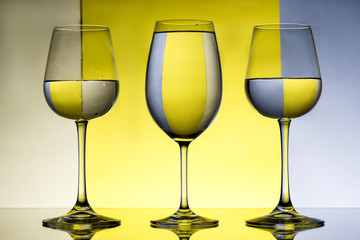 Obraz na Plexi Minimalistyczny Three wineglasses with water over grey and yellow background.