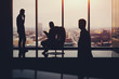 Silhouettes of business people: businessman with businesswoman waiting for their third colleague which is already coming to start meeting, high floor, winter cityscape outside, luxury office interior