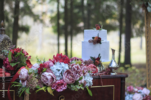Wall Murals Cemetery wedding cake on table with flowers in forest with mirror