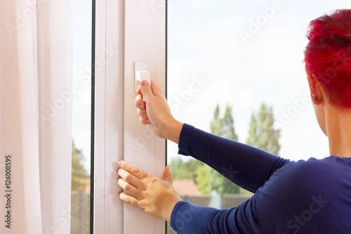 Valokuva  Frau sichert das Fenster