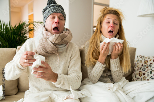 Obraz Sick couple catch cold. Man and woman sneezing, coughing, got flu, having runny nose. - fototapety do salonu