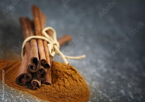 Fotografie, Obraz  Cinnamon sticks and ground cinnamon, selective focus