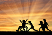 Happy Boy In Wheelchair Playing With Children Sunset