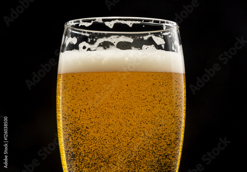 Photo  glass of beer with bubbles and foam on black closeup.