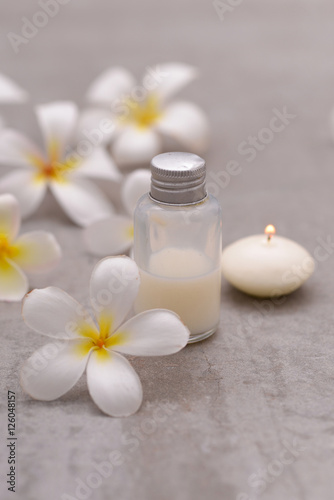 Poster Spa Spa stone with frangipani ,massage oil ,candle on grey background.