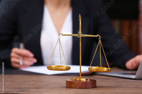 Leinwand Poster Scales of justice on wooden table and female lawyer on background