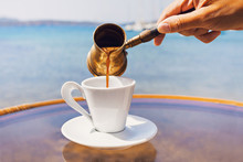 Female Hand Pouring Traditional Greek Coffee In A Cafe With A Sea On The Background, Greece. Traditional Culture, Travel, Vacations, Food And Drink Concept
