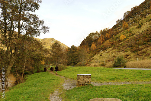 Photo  A girl walks into the distance in a Scottish Highland glen