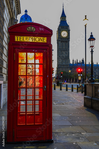 Poster Rouge, noir, blanc Famous English red telephone boxes with Big Ben in London at nig