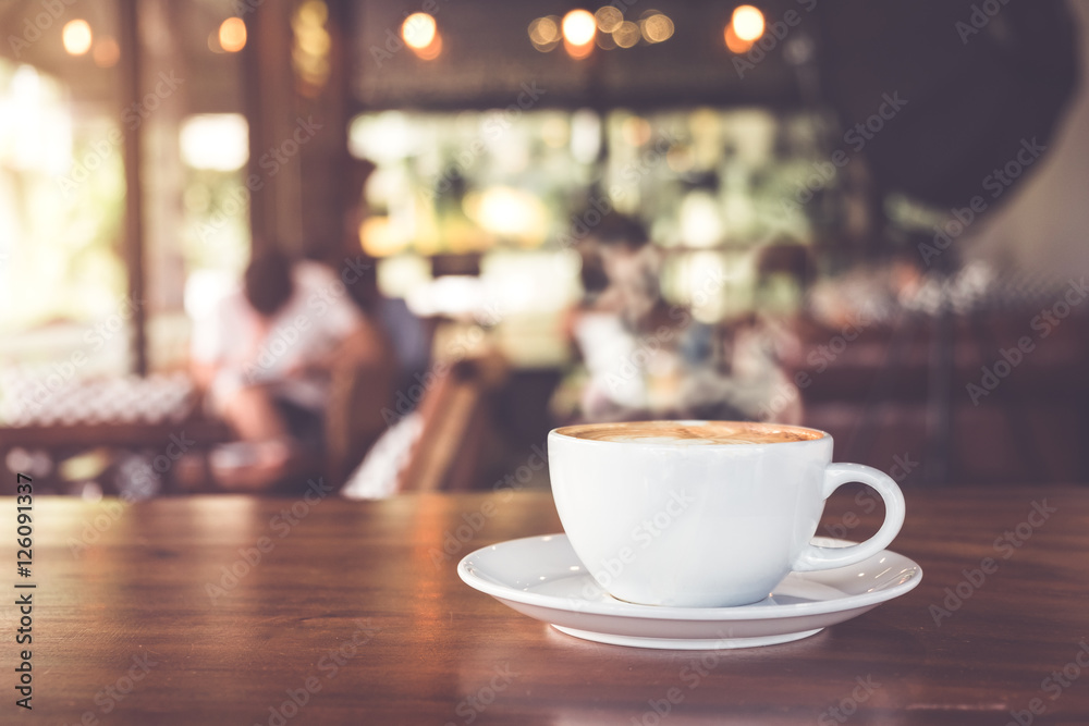 Fototapeta Cup of hot coffee on table in cafe with people. vintage and retro color effect - shallow depth of field