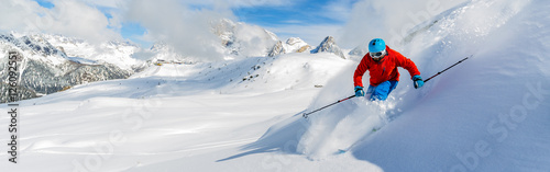 Skier skiing downhill in high mountains in fresh powder snow. Sa Canvas Print