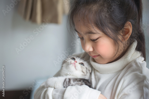 Photo  Happy little Asian girl hugging lovely scottish fold kitten