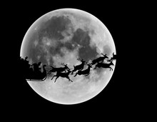 Silhouette Of Santa Claus And Reindeer Riding Sleigh In Front Of Full Moon In Night Sky