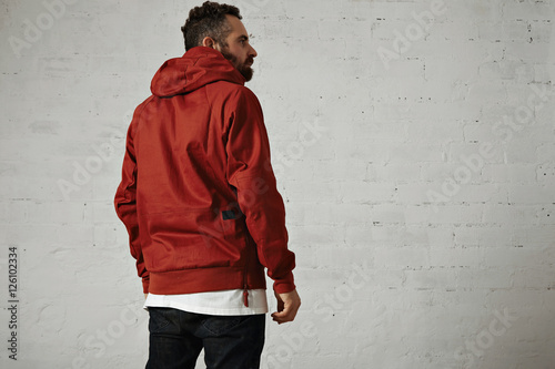 Back shot of a stylish bearded guy wearing a brick red anorak, black jeans and w Wallpaper Mural