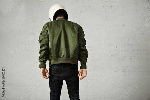 Leinwand Poster Athletic young model in skinny jeans, green bomber jacket and white motorcycle h