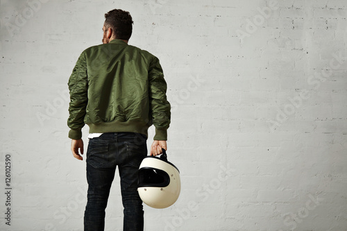 Fotografia Back shot of a hip bearded pilot in green bomber jacket, skinny jeans and with a
