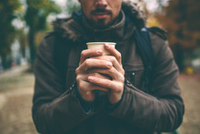 Man In Coat Holding A Cup Of C...