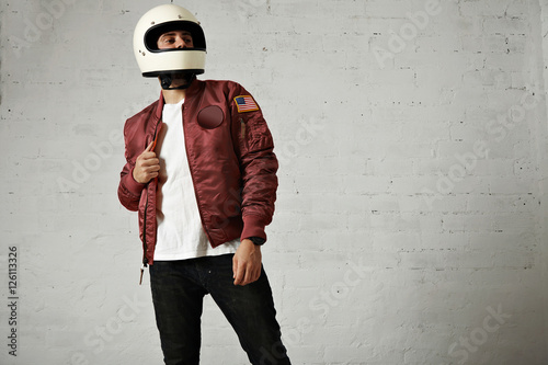 Carta da parati Proud looking motorbiker in a plain white helmet, bordeaux nylon bomber jacket,