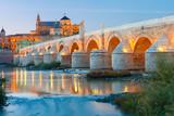 Illuminated Great Mosque Mezquita - Catedral de Cordoba and Roman bridge across Guadalquivir river, Cordoba, Andalusia, Spain