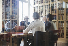 Lawyers Sitting At Table During Meeting Seen Through Glass In Law Library