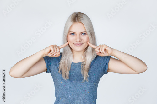 Valokuva  Young woman with fingers pointing to her dimples