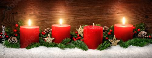 Advent Dekoration mit drei Kerzenflammen, Schnee, Tannenzweigen und Holz Hintergrund