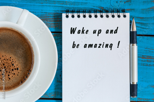 Photo  Wake Up and Be Amazing message text written in notepad near morning cup of coffe