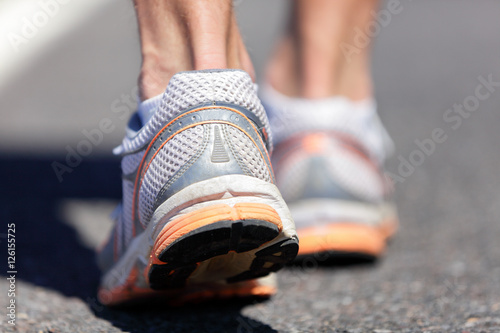 Running shoes feet closeup man jogging on road Canvas Print