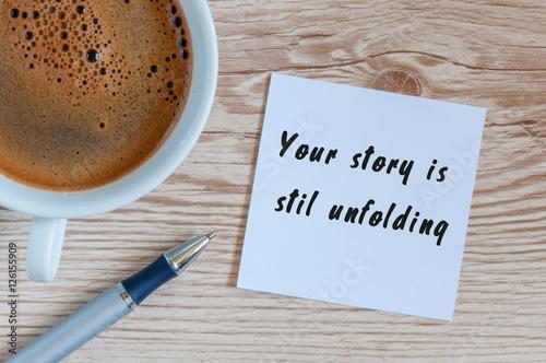 Fotografie, Obraz  Your Story Is Still Unfolding motivation inscription at notepad near morning cup