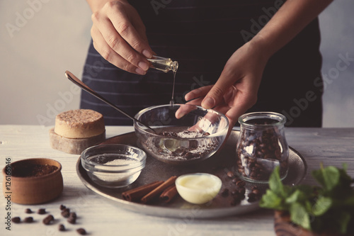 Fototapeta Woman making coffee body scrub on wooden table