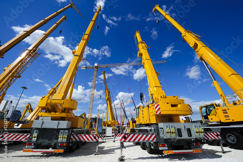 фотография Mobile construction cranes with yellow telescopic arms and big tower cranes in s