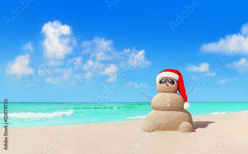 Sandy snowman in Christmas Santa hat and sunglasses at beach Wallpaper Mural