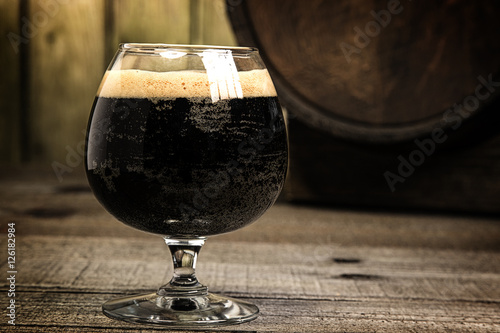Foto Russian Imperial Stout in snifter glass on wood background and b