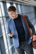 Man on smart phone - young business man texting in airport. Casual urban professional businessman using smartphone app smiling happy inside office building or airport.