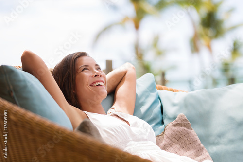 Fototapeta Home lifestyle woman relaxing enjoying luxury sofa patio furniture on outdoor patio living room. Happy lady lying down on comfortable pillows daydreaming thinking. Beautiful young Asian chinese girl. obraz