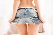 Back Of Young Woman In Denim Mini Skirt. Perfect Body Of Modern Sexy Lady. Sex, Seduction, Passion, Youth, Summer, Fashion Concept