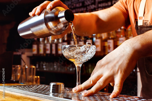 Fotografia  Male bartender is making cocktail holding shaker with pouring alcohol