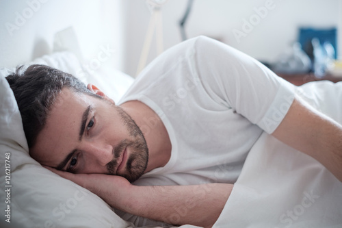 Fotografie, Obraz  Depressed man lying in his bed and feeling bad