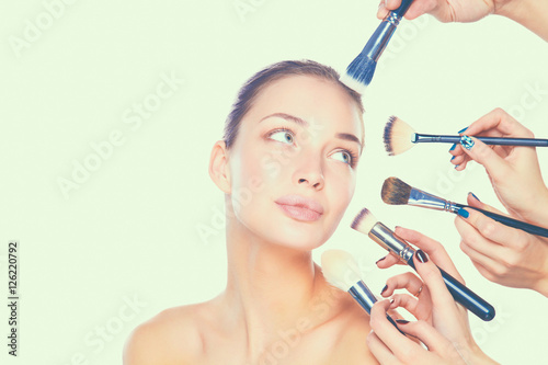 Tela  Young woman with make up brush, isolated on white background