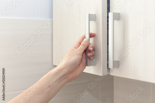 Female hand open the cupboard doors, close up Canvas Print