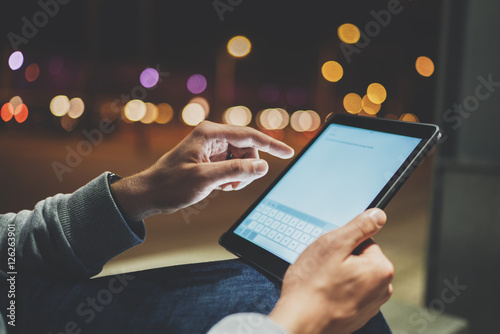 Fotografia  Side view of male hands using modern digital tablet outdoor, night lights and bo