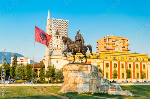 Photo Skanderbeg square with flag, Skanderbeg monument and The Et'hem Bey Mosque in the center of Tirana city, Albania