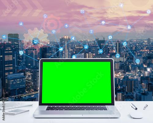 500_F_126268517_OnarA77FmlidXeZ2Yb6D86SLpyVvSzfg blank green screen laptop computer with night cityscape and digital