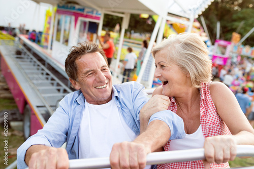 Stampa su Tela Senior couple on a ride in amusement park