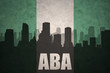 abstract silhouette of the city with text Aba at the vintage nigerian flag