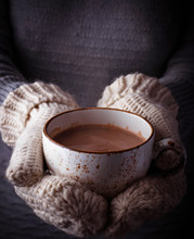 Woman In Mittens Holding A Cup Of Hot Chocolate