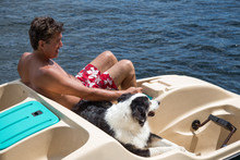 Man And Dog In Paddle Boat