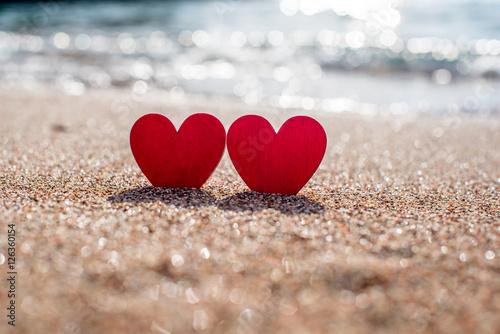 Fotografia  romantic symbol of two hearts on the beach